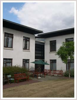 An image of sheltered housing with benches outside in the garden