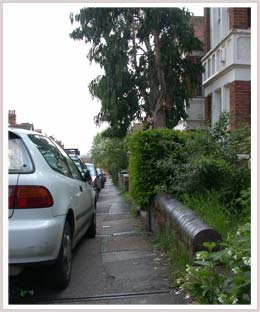 An image of a footway with cars parked halfway on it
