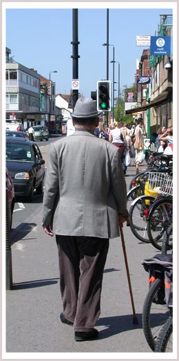 An image of a man walking with a cane down the street