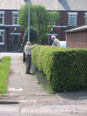 photograph of two men having a conversation from a footpath