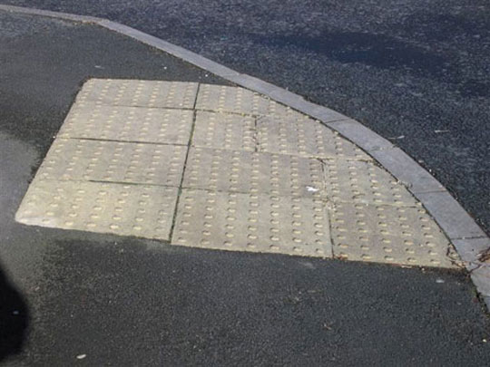 A tactile dropped kerb which contrasts with its surround surfaces
